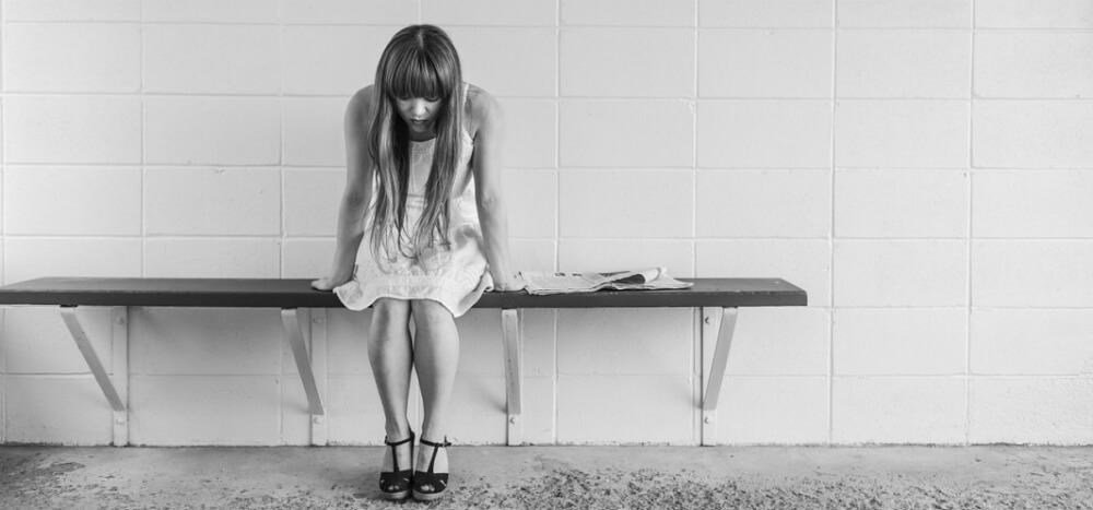 Depressed girl sitting on a bench
